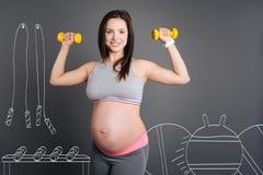 Szczęśliwy uśmiechnięty kobieta w ciąży robi sportów ćwiczeniom zdjęcia royalty free