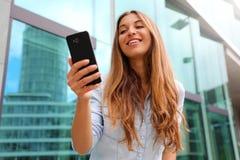 Szczęśliwy uśmiechnięty kobiety odprowadzenie w dzielnica biznesu używać smartphone Niski k?t obrazy stock