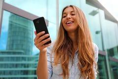 Szczęśliwy uśmiechnięty kobiety odprowadzenie w dzielnica biznesu używać smartphone Niski k?t fotografia royalty free
