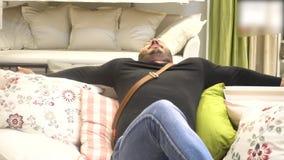 Szczęśliwy uśmiechnięty mężczyzna z brody relaksującym i uśmiechniętym obsiadaniem na kanapie zdjęcie wideo