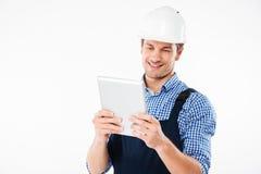 Szczęśliwy uśmiechnięty męski budowniczy używa komputer osobisty pastylkę Fotografia Royalty Free
