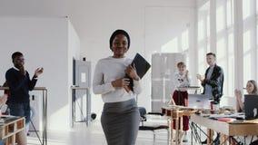 Szczęśliwy uśmiechnięty młody Afrykański żeński kierownik wchodzić do nowego biuro z pudełkiem, witającym kolegi zwolnionego temp zbiory