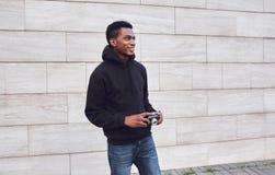 Szczęśliwy uśmiechnięty młody afrykański mężczyzna z rocznika filmu kamerą w czarnym hoodie odprowadzeniu na miasto ulicie obrazy royalty free