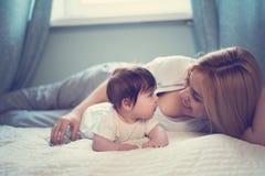 Szczęśliwy uśmiechnięty matki i dziecka lying on the beach na łóżku w domu obraz royalty free