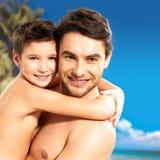 Szczęśliwy uśmiechnięty ojciec ściska syna przy tropikalną plażą zdjęcie royalty free