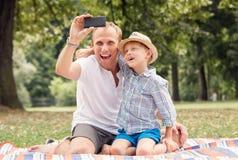 Szczęśliwy uśmiechnięty ojciec i syn bierzemy jaźń obrazek z telefonem Obraz Stock