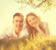 Szczęśliwy uśmiechnięty pary lying on the beach na trawie fotografia royalty free