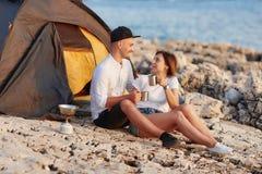 Szczęśliwy uśmiechnięty pary siedzieć twarz w twarz przy skalistą plażą na pobliskim namiocie obrazy royalty free