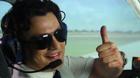 Szczęśliwy uśmiechnięty pilot pokazuje aprobaty podpisuje podczas gdy siedzący w kokpicie, zawód zbiory