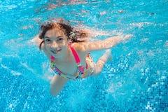 Szczęśliwy uśmiechnięty podwodny dziecko w pływackim basenie Zdjęcia Royalty Free