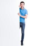 Szczęśliwy uśmiechnięty przystojny młodego człowieka spojrzenie out od pustego sztandaru. Fotografia Royalty Free
