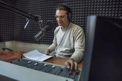 Szczęśliwy uśmiechnięty samiec radia podawca lub gospodarz z hełmofonami na głowie opowiada w mikrofon w radio stacji, portret pr fotografia royalty free