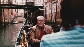 Szczęśliwy uśmiechnięty starszy Europejski mężczyzna i kobieta w gondoli cieszy się Wenecja wycieczki turysycznej kanałową wyciec zdjęcie wideo
