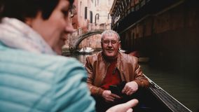 Szczęśliwy uśmiechnięty starszy Europejski męski turystyczny słuchanie stara kobieta w gondoli podczas Wenecja wycieczki turysycz zbiory