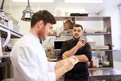 Szczęśliwy uśmiechnięty szef kuchni i kucharz przy restauracyjną kuchnią Fotografia Stock