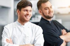 Szczęśliwy uśmiechnięty szef kuchni i kucharz przy restauracyjną kuchnią zdjęcie stock