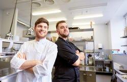 Szczęśliwy uśmiechnięty szef kuchni i kucharz przy restauracyjną kuchnią Obraz Stock