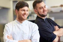 Szczęśliwy uśmiechnięty szef kuchni i kucharz przy restauracyjną kuchnią Obrazy Royalty Free