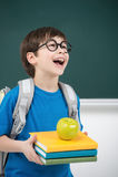 Szczęśliwy uczeń. Szczęśliwy mały uczeń trzyma książkową stertę a Obraz Stock