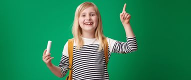 Szczęśliwy uczeń z pokojem wskazuje przy coś kreda obrazy royalty free