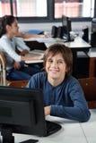Szczęśliwy Uczniowski obsiadanie Z komputerem Przy biurkiem Obrazy Stock