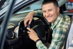 Szczęśliwy właściciel trzyma jego ręki na kierownicie pojazd zdjęcie royalty free