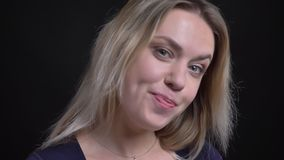 Szczęśliwy w średnim wieku blondynka bizneswoman w błękitnych bluzka uśmiechach contentedly i tajemniczo w kamerę na czerni zbiory
