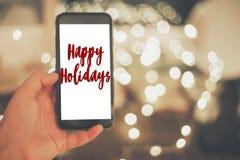 Szczęśliwy wakacje teksta znak na ręce trzyma mądrze telefon z pustym Zdjęcia Stock