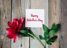 Szczęśliwy walentynka dnia tekst na prześcieradle papier, czerwony kwiat na starym nieociosanym drewnianym tle obraz stock