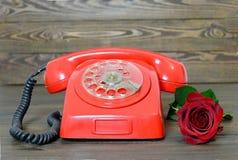 Szczęśliwy walentynka dzień: Rocznik czerwieni telefon i czerwieni róża Zdjęcia Stock