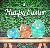Szczęśliwy Wielkanocny dzień: Trzy Kolorowej przezroczystości szklany jajko na drewnie royalty ilustracja