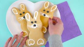 Szczęśliwy Wielkanocny koszt stały z Wielkanocnego królika cukierkiem na drewno stole i ciastkami zbiory