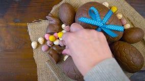 Szczęśliwy Wielkanocny koszt stały z Wielkanocnymi jajkami i dekoracjami na drewnianym tle zbiory