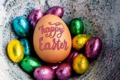 Szczęśliwy wielkanocy 2017 literowanie na jajku wykładał z małą czekoladą eg. Fotografia Royalty Free