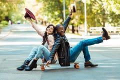 Szczęśliwy wielokulturowy pary obsiadanie na longboard na ulicie i wydźwignięcie rękach fotografia stock