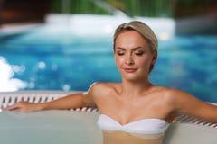 Szczęśliwy womani obsiadanie w jacuzzi przy poolside Zdjęcie Royalty Free