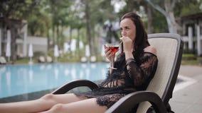 Szczęśliwy wooman obsiadanie na słońca lounger pić koktajlem i basenem zbiory