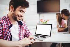 Szczęśliwy wykonawczy texting w spotkaniu przy kreatywnie biurem Obraz Stock