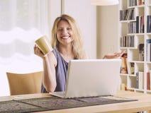 Szczęśliwy z jej laptopem w domu zdjęcie stock