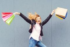 Szczęśliwy z podnieceniem dziewczyny doskakiwanie z papierowymi torbami po robić zakupy obrazy stock