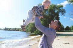 Szczęśliwy z podnieceniem ojciec i syn bawić się na lato plaży, cieszymy się życie zdjęcie stock