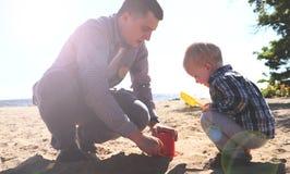 Szczęśliwy z podnieceniem ojciec i syn bawić się na lato plaży, cieszymy się życie fotografia stock