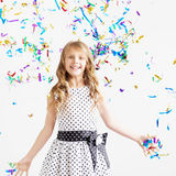 Szczęśliwy z podnieceniem roześmiany dzieciak pod iskrzastymi confetti brać prysznić obraz royalty free