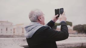 Szczęśliwy z podnieceniem starszy męski turysta bierze fotografię antycznego miasta budynki w Rzym, Włochy używać smartphone zwol zdjęcie wideo