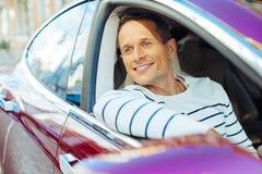 Szczęśliwy zadowolony mężczyzna obsiadanie w jego samochodzie Obrazy Royalty Free
