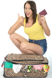 Szczęśliwy Zadowolony Z podnieceniem młodej kobiety klęczenie Za walizką Trzyma paszport Obrazy Stock