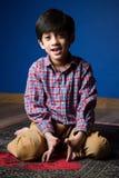 Szczęśliwy zdrowy chłopiec obsiadanie na dywaniku ciemniutki Obrazy Royalty Free