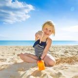 Szczęśliwy zdrowy dziecko wskazuje przy słońce ekranem w swimwear na plaży Obrazy Stock