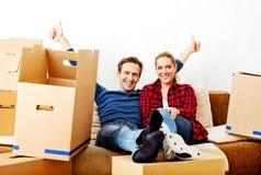 Szczęśliwy zmęczony pary obsiadanie na leżance w nowym domu z cordboard boksuje wokoło Obraz Royalty Free