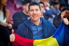 """Szczęśliwy zwolennik trzyma Rumuńską flagę państowową w rękach przy międzynarodowym wydarzenia sportowego †""""mężczyzna w stojaka fotografia royalty free"""